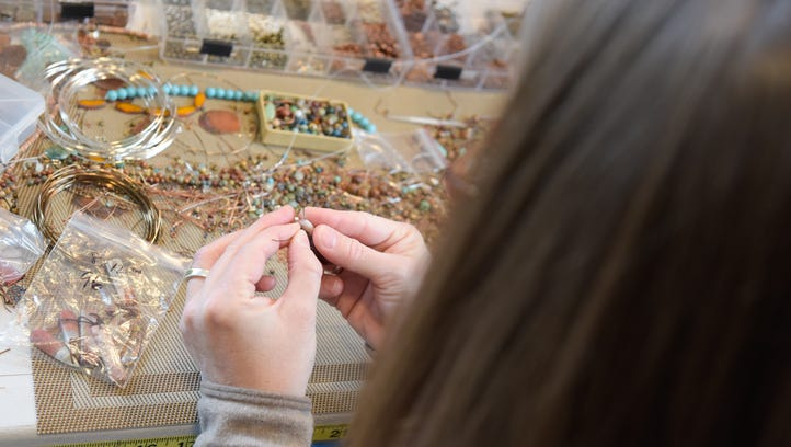 Linda Blume, Eatontown, is the owner/artist at Rustica Jewelry. Here she threads an earring in her studio.