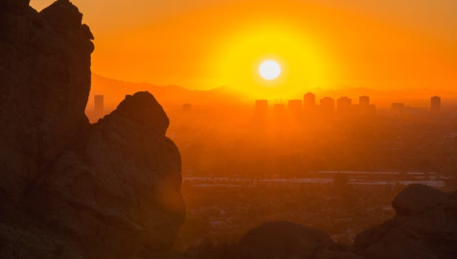 A sunset over downtown Phoenix, Arizona taken from the Echo Canyon trail on Camelback Mountain.