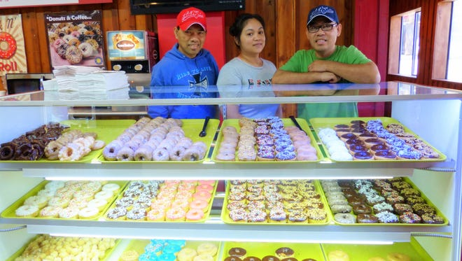 From left, Rick Preap, Sandy Om and Danny Preap take a second to show off their tasty goodies.