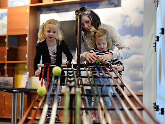 Heather Boles and her daughters Kayla, 4, and Kylie, 2, play with a kinetic energy exhibit at the Fort Collins Museum of Discovery on Tuesday, February 16, 2016. Moms get free admission on  Mother's Day.