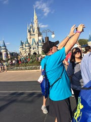 Gary Niemeier, a staff member at McGary Middle School takes a photo of the parade on Saturday afternoon with the Magic Kingdom castle in the background. Niemeier said the week has been all about bonding. This is the first year students from McGary have been included on the Cops Connecting with Kids trip.