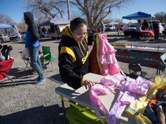 Yvonne Begay organizes her aprons Friday at her table during the Shiprock Chapter Christmas Bazaar at the Shiprock Chapter House.