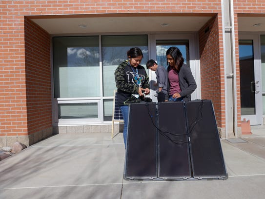 Students Keona Hosteen, left, Sky Harper and Miauaxochitl Haskie work on their solar panel project on Wednesday at Navajo Prep in Farmington.