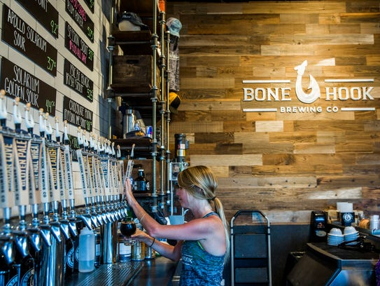 Bartender Erin O'Rourke pours beer from a tap at Bone
