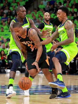 Minnesota Timberwolves guard Jeff Teague (0) and center Gorgui Dieng, back left, try to block Phoenix Suns guard Isaiah Canaan (2) in the first quarter of an NBA basketball game on Saturday, Dec. 16, 2017, in Minneapolis.