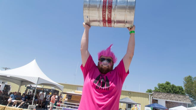 A member of the Black Bottle team raises a keg over his head during the opening ceremony of the 2016 Brewer's Olympics.