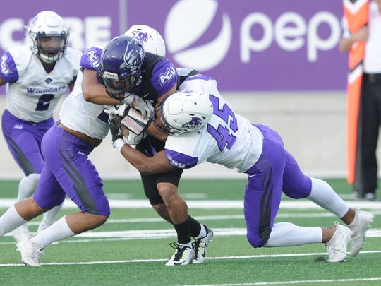 ACU's Qua'Shawn Washington, right, and Landry Hutchins tackle receiver D.J. Fuller after a catch in the first half in the Wildcats' spring game Friday, April 6, 2018 at Wildcat Stadium.