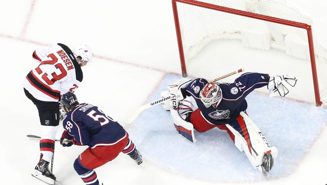 Columbus Blue Jackets' Sergei Bobrovsky, right, of Russia, makes a save as teammate David Savard, center, and New Jersey Devils' Stefan Noesen fight for the rebound during the first period of an NHL hockey game Tuesday, March 7, 2017, in Columbus, Ohio. The Blue Jackets defeated the Devils 2-0. (AP Photo/Jay LaPrete)