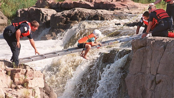 An 8-year-old boy makes his way across the falls to safety in 1998 on a ladder bridge provided by Sioux Falls firefighters. Brown was stranded on the rocks in Falls Park after he said he had dropped his tennis shoes into the water and was trying to retrieve them.