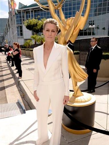 "In this photo provided by Invision for the Television Academy, Robin Wright arrives at the 66th Primetime Emmy Awards at the Nokia Theatre L.A. Live on Monday, Aug. 25, 2014, in Los Angeles. The ""House of Cards"" actress eluded red carpet watchers in her cream Ralph Lauren jumpsuit with a plunging tuxedo jacket front and virtually no back at all. (AP Photo/Invision for the Television Academy, Dan Steinberg)"