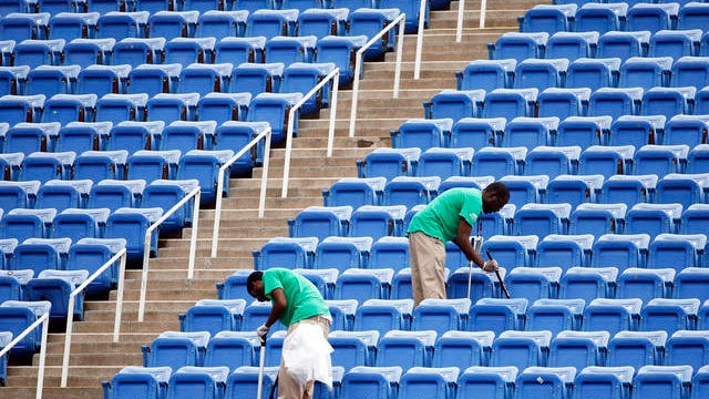 In this Sept. 10, 2015 file photo, workers clean the empty stands in Arthur Ashe Stadium after the women's semifinal matches were postponed because of rain at the U.S. Open tennis tournament in New York. Addressing airborne threats like the novel coronavirus is a particular challenge, especially when they can stick around for hours wherever they might land.
