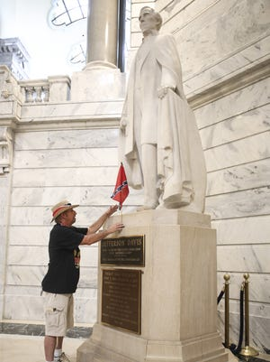 Hames Hendrickson of Corbin, Kentucky, places a Confederate flag on the Jefferson Davis statue in the rotunda at the state Capitol following the Confederate Veterans rally. July 24, 2015