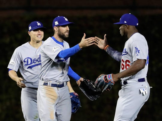 Enrique Hernandez #14, Chris Taylor #3, and Yasiel Puig #66 of the Los Angeles Dodgers celebrate after beating the Chicago Cubs 6-1 during game three of the National League Championship Series at Wrigley Field on October 17, 2017 in Chicago.