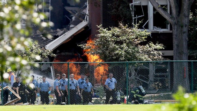 Emergency personnel move away as a gas fire continues to burn following an explosion at Minnehaha Academy on Aug. 2, 2017, in Minneapolis, Minn. Several people are unaccounted for after an explosion and partial building collapse Wednesday at a Minneapolis school, fire officials said.