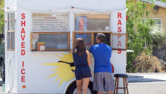 Some find temporary relief from the heat at a shaved ice stand located at the corner of West Pine and North Copper streets.