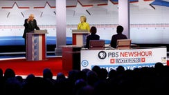 Bernie Sanders speaks as Hillary Clinton looks on during