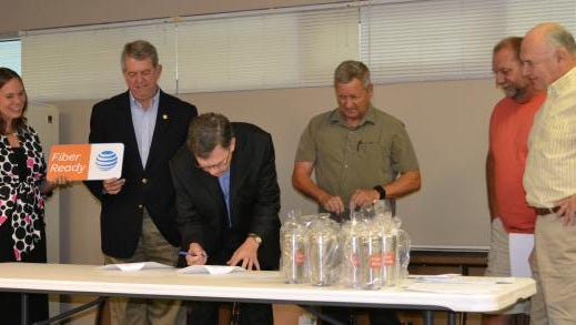 Hood Harris President of AT&T Kentucky, signs the fiber ready agreement during a ceremony August 17 at Ervin Cable Construction in the Sturgis Industrial Park.  On hand for the signing were, from the left, State Rep. Suzanne Miles; State Sen. Dorsey Ridley, Harris; Ervin Cable part-owner Gary Ervin; Sturgis Airport Manager Ronnie Hollies and Union County Air Board member Bill Pierce.