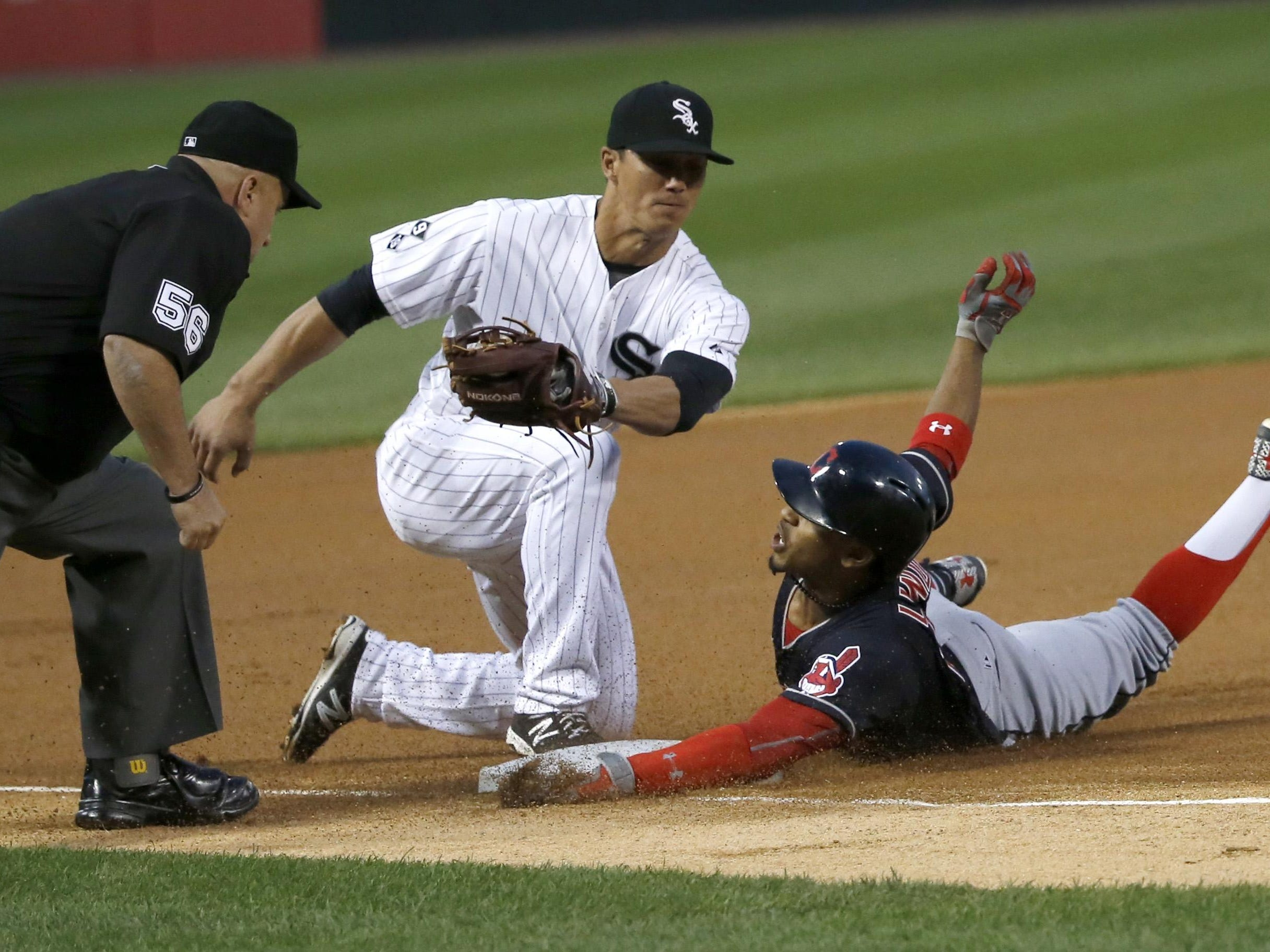 Cleveland Indians' Francisco Lindor slides safely into third for a triple, beating a throw from Chicago White Sox left fielder Melky Cabrera to third baseman Tyler Saladino, as umpire Eric Cooper watches, during the first inning of a baseball game Wednesday, Sept. 9, 2015, in Chicago. (AP Photo/Charles Rex Arbogast)