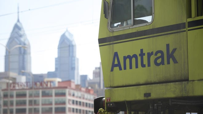 Amtrak train is parked with a view of the skyline near 30th Street Station.