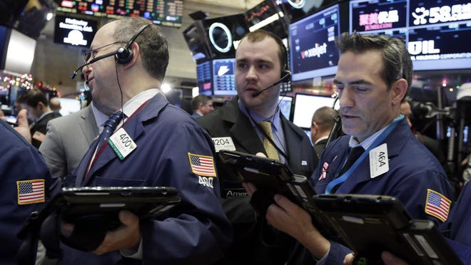 Traders Gordon Charlop, left, Nathan Wisniewski, center, and Gregory Rowe, work on the floor of the New York Stock Exchange.