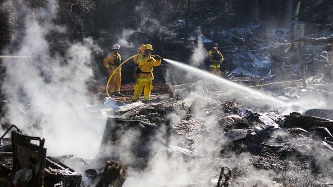 Firefighters work to contain embers on the remains of a house destroyed by the Clayton Fire in Lower Lake, California, Aug. 15th, 2016. A northern California wildfire grew rapidly over the weekend, destroying homes and forcing 4,000 residents to flee, authorities said.