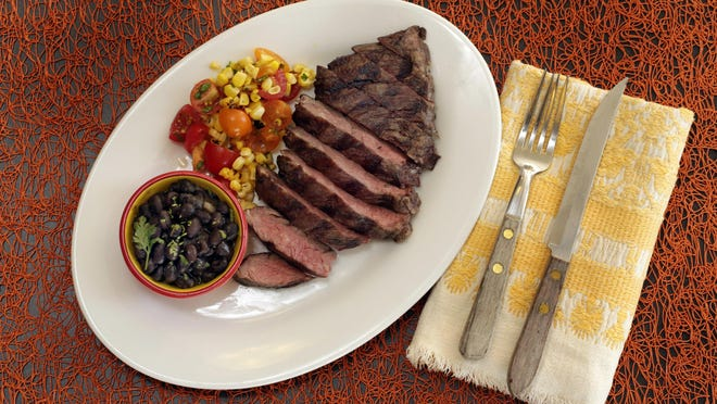 Skirt steak is served with beer-braised black beans and corn salsa.