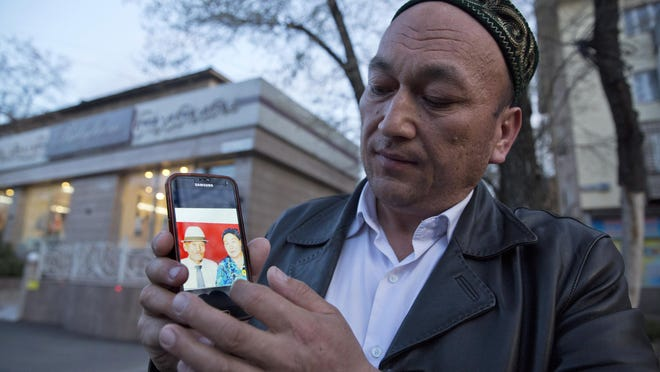 Omir Bekali shows a photo of his parents, whom he believes have been detained in China, in Almaty, Kazakhstan.