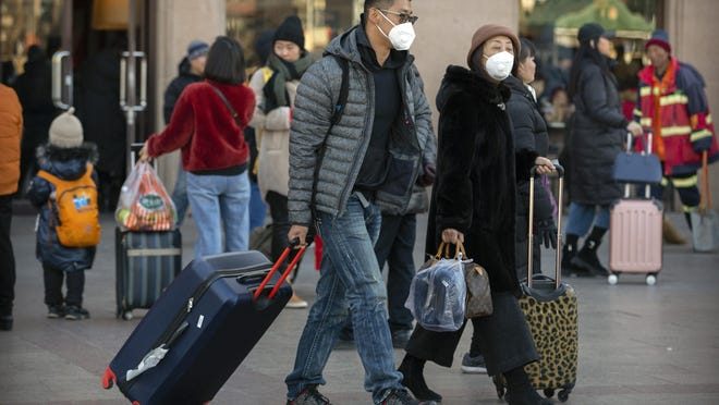 Travelers wear face masks as they walk outside of the Beijing Railway Station in Beijing, Monday, Jan. 20, 2020. China reported Monday a sharp rise in the number of people infected with a new coronavirus, including the first cases in the capital. The outbreak coincides with the country's busiest travel period, as millions board trains and planes for the Lunar New Year holidays. (AP Photo/Mark Schiefelbein)