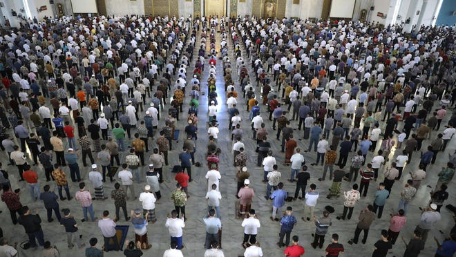 Muslim men perform Friday prayer at the distance of about one meter (3 ft) to each other as a social distancing effort to prevent the spread of new coronavirus outbreak at Al Akbar mosque in Surabaya, East Java, Indonesia, Friday, March 20, 2020. The vast majority of people recover from the new coronavirus. According to the World Health Organization, most people recover in about two to six weeks, depending on the severity of the illness. (AP Photo/Trisnadi)