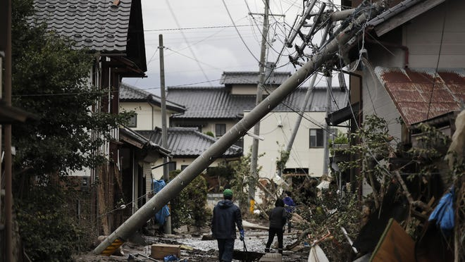 Residents walk along the mud-covered road in a neighborhood devastated by Typhoon Hagibis on Oct. 15 in Nagano, Japan.