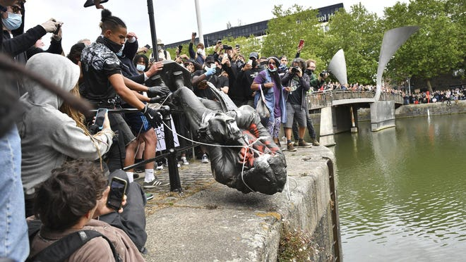 Protesters throw a statue of slave trader Edward Colston into Bristol harbour, during a Black Lives Matter protest rally, in Bristol, England, on Sunday in response to the recent killing of George Floyd by police officers in Minneapolis, which has led to protests in many countries and across the US.