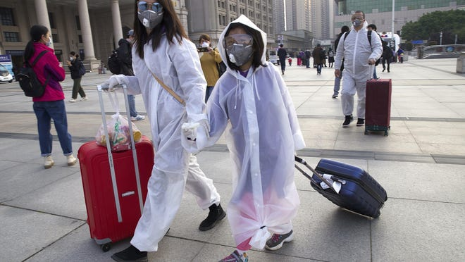 Passengers wearing face masks and rain coats to protect against the spread of new coronavirus walk outside of Hankou train station after of the resumption of train services in Wuhan in central China's Hubei Province, Wednesday, April 8, 2020. After 11 weeks of lockdown, the first train departed Wednesday morning from a re-opened Wuhan, the origin point for the coronavirus pandemic, as residents once again were allowed to travel in and out of the sprawling central Chinese city.