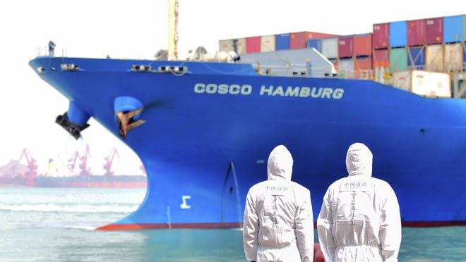 In this March 31, 2020 photo, workers in protective suits stand near a COSCO container ship docked at a port in Qingdao in eastern China's Shandong Province. China's government reported Tuesday, April 14, 2020 that exports fell further in March compared with February amid a global economic slowdown caused by the coronavirus pandemic.