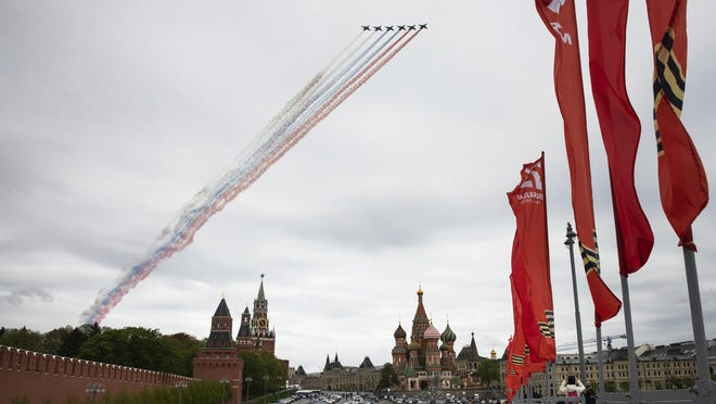 Russian Air Force Su-25 jets fly over Red Square leaving trails of smoke in colors of national flag to mark the 75th anniversary of the Nazi defeat in World War II in Moscow, Russia, Saturday, May 9, 2020. A massive Victory Day parade on Red Square was cancelled due to the coronavirus outbreak, but Russia marked the holiday with the flyby.