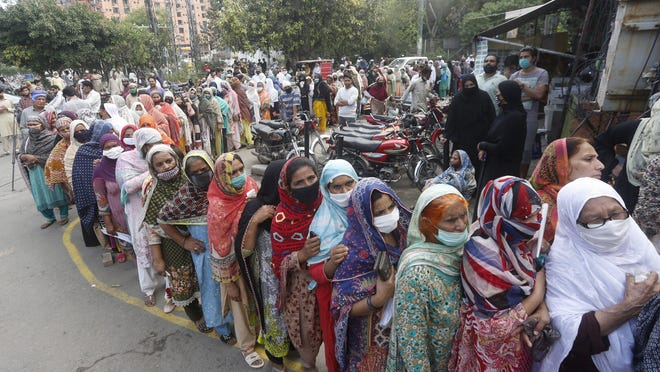 People stand outside a government office to get their identity cards verified to receive grant from government during a nationwide lockdown to try to contain the outbreak of the new coronavirus, in Lahore, Pakistan, Monday, May 4, 2020.