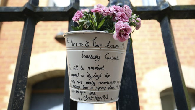 Flowers and a message were left Sunday June 21, 2020, at the gateway to Forbury Gardens park in Reading, England, following a multiple stabbing attack in the park Saturday evening which left three people dead and another three seriously injured.