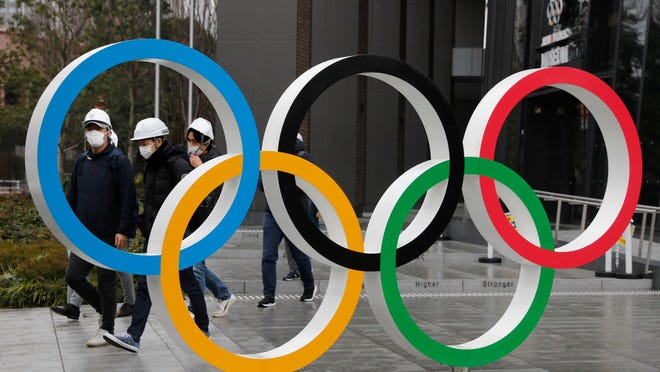"In this March 4, 2020, file photo, people wearing masks walk past the Olympic rings near the New National Stadium in Tokyo. It's been 2 1/2 months since the Tokyo Olympics were postponed until next year because of the COVID-19 pandemic. So where do the games stand? So far, many ideas about how the Olympic can take place are being floated by the International Olympic Committee, Japanese officials and politicians, and in unsourced Japanese newspaper articles coming from local organizers and politicians. The focus is on soaring costs, fans, or no fans, possible quarantines for athletes, and cutting back to only ""the essentials."""