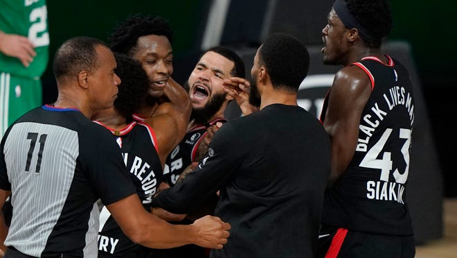 Teammates mob Toronto Raptors' OG Anunoby, second player from left, after Anunoby's winning shot at the buzzer Thursday night against the Celtics.