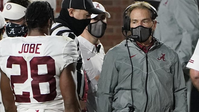 A masked Alabama coach Nick Saban speaks with defensive back Josh Jobe (28) during the second half of the team's NCAA college football game against Mississippi in Oxford, Miss., Saturday, Oct. 10, 2020. Alabama won 63-48.