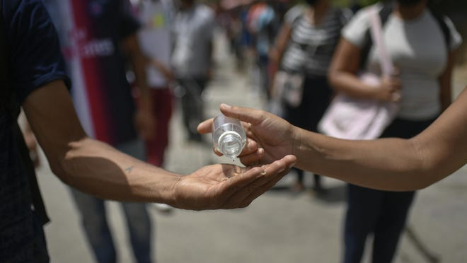 A shopper shares disinfectant with a fellow shopper while standing in line outside the Coche food market in Caracas, Venezuela, Saturday, July 11, 2020, amid a government-ordered lockdown to curb the spread of the new coronavirus.