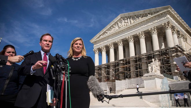 Michigan Attorney General Bill Schuette, left, speaks outside the Supreme Court during arguments last fall over affirmative action.
