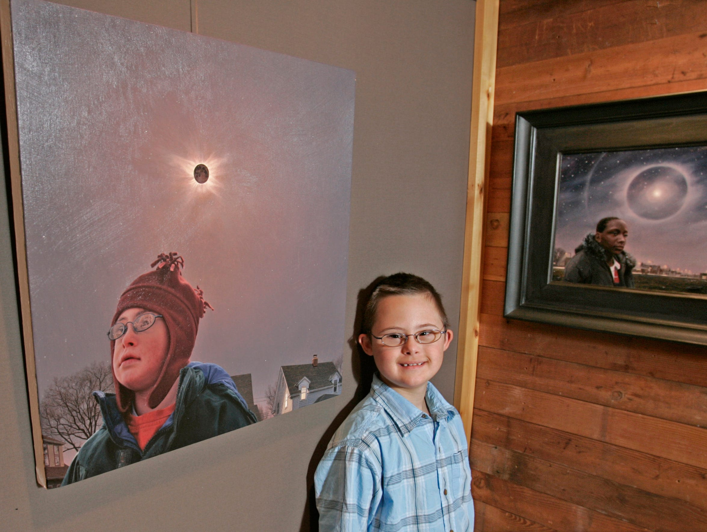 In 2006, Sam Lenz stands near a portrait of himself