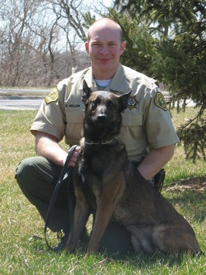 A federal lawsuit accuses Pottawattamie County law enforcement, including Deputy Brian Miller, shown with his drug dog Francesco, of improperly using traffic stops and a drug-detecting dog to gain access to vehicles and seize money from motorists under Iowa's much-criticized civil forfeiture laws.