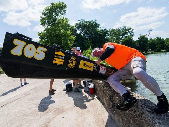 Wayne Thorp works to move his team's canoe past a barrier