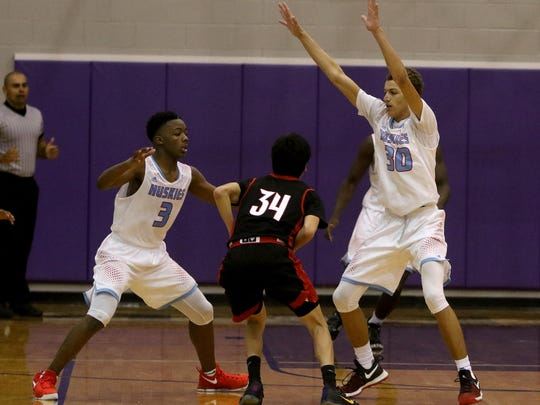 Hirschi's Mark Harrell (3) and Trae Jones (30) guard Mineral Wells Riley Scott in the Region I-4A Area playoff against Mineral Wells Friday, Feb. 24, 2017, in Jacksboro. Hirschi defeated Mineral Well 51-49.