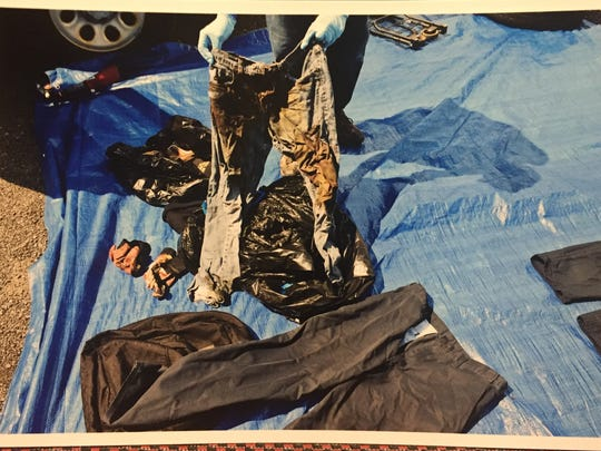 Photo of jeans that prosecutors say contains blood from Craig Rideout and DNA from Colin Rideout. Defense attorneys say it shows technicians standing on the tarp and items of evidence touching each other.