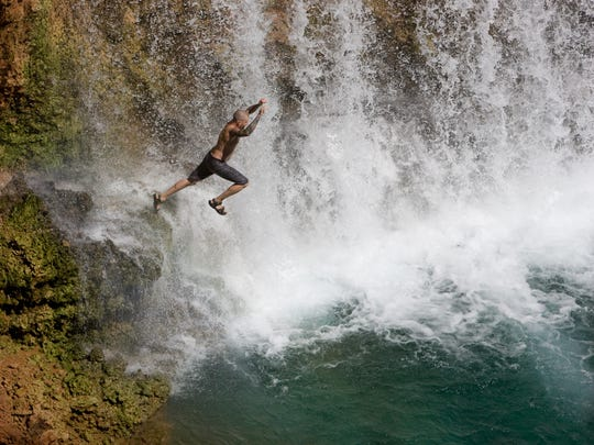 John Luttman, 33, of Tucson, jumps from a rock at Rock