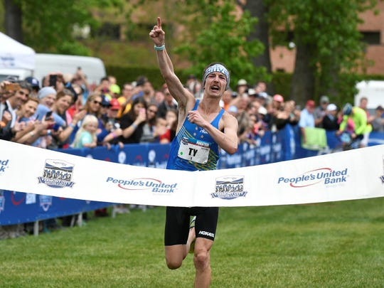 Tyler Andrews of Concord, Massachusetts, crosses the Vermont City Marathon finish line as the men's winner. This is the second-straight time he's won, and the third overall.