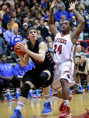 Carmel's Ryan Cline pulls up before taking a shot around North Central's Carl Drummer in the second half of the game at North Central High School on Friday, Dec. 12, 2014. Carmel lost to North Central 66-59.
