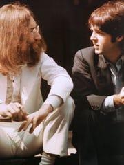 John Lennon, left, and Paul McCartney talk during the